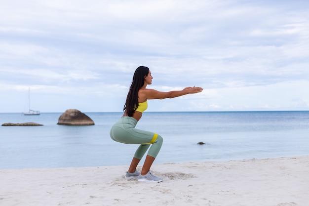 해변에서 다채로운 스포츠 착용에 매력적인 젊은 여자