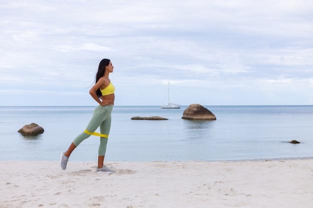 Привлекательная молодая женщина в красочной спортивной одежде на пляже