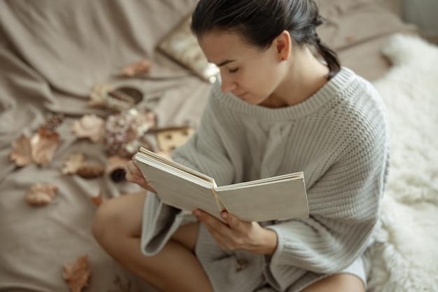 ベッドで本を読んで居心地の良いニットセーターの魅力的な若い女性。
