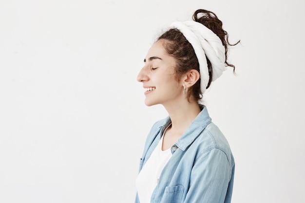 Привлекательная молодая женщина в пиджаке и джинсовой рубашке, отдыхая в помещении, с милой улыбкой и закрытыми глазами, позирует на белой стене с копией пространства для вашего текста или рекламного контента