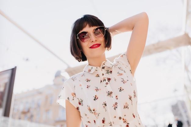 ロマンチックな笑顔でポーズをとるエレガントなサングラスの魅力的な若い女性。通りで身も凍るような白い服を着た短い髪のヨーロッパの女性の屋外の肖像画。