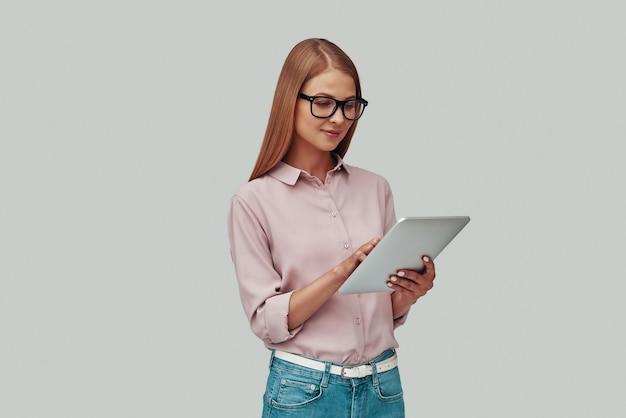 Привлекательная молодая женщина в очках с помощью цифрового планшета и улыбается, стоя на сером фоне