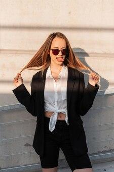 スタイリッシュなサングラスでファッショナブルな美しい若者の服を着た魅力的な若い女性が立って、晴れた明るい日にヴィンテージの壁の近くに舌を示しています。若者の衣装の面白いしかめっ面のクールな女の子モデル。