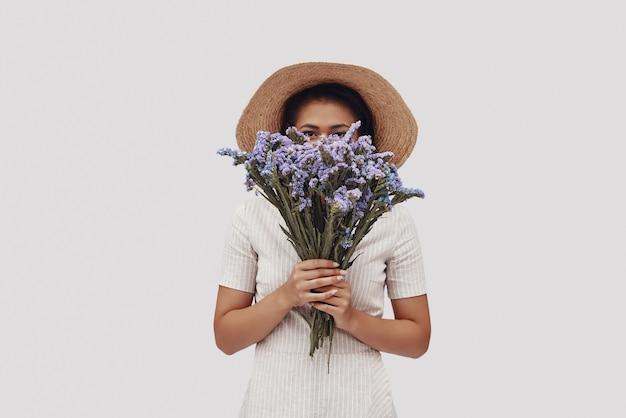 Привлекательная молодая женщина в шляпе смотрит в камеру и закрывает лицо букетом, стоя на сером фоне