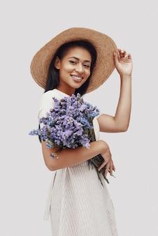 Привлекательная молодая женщина в шляпе смотрит в камеру и улыбается, стоя на сером фоне