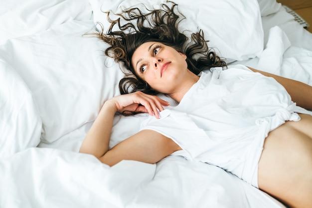 침대에서 란제리에서 매력적인 젊은 여자