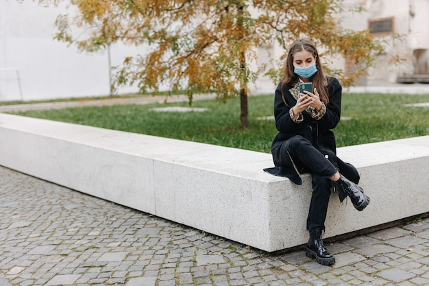 屋外に座って、現代のスマートフォンを使用して医療マスクの魅力的な若い女性。人、技術、コロナウイルスの概念。