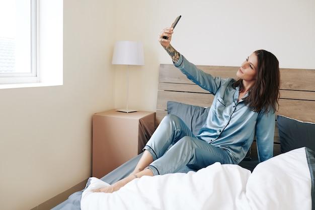 Привлекательная молодая женщина в шелковой пижаме сидит на кровати и делает селфи после пробуждения