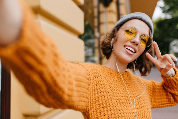 寒い日の屋外散歩中にピースサインでselfieを作るスポーツ帽子の魅力的な若い女性