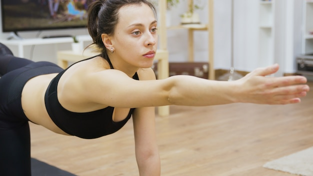 リビングルームでヨガマットに取り組んでいるスポーツウェアの魅力的な若い女性。
