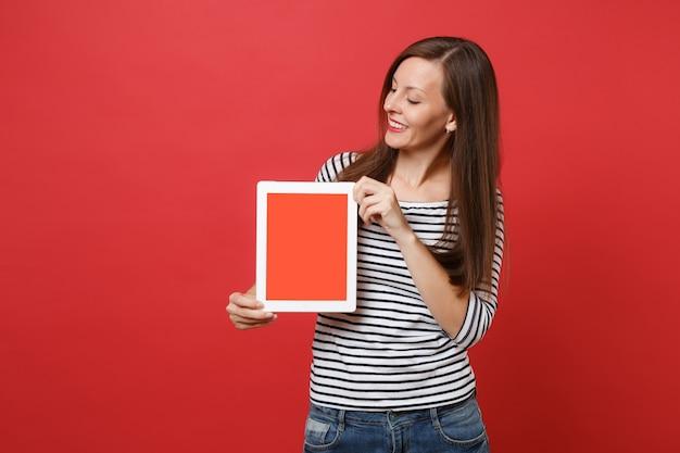 줄무늬 옷을 입은 매력적인 젊은 여성이 빨간색 배경에 격리된 손에 빈 검은색 빈 화면이 있는 태블릿 pc를 보고 있습니다. 사람들은 진심 어린 감정 라이프 스타일 개념입니다. 복사 공간을 비웃습니다.