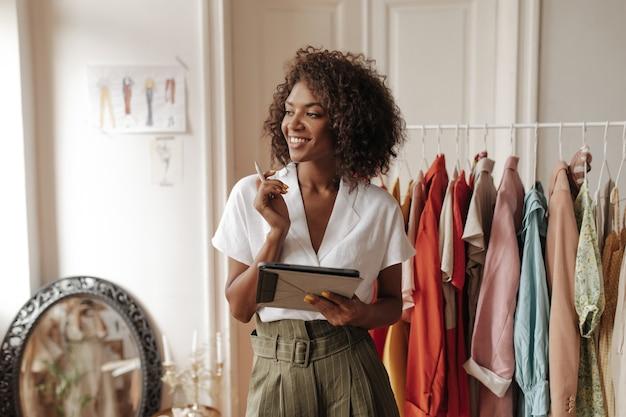 세련된 흰색 블라우스와 카키색 반바지를 입은 매력적인 젊은 여성이 시선을 돌리고 미소 짓고 아늑한 방에서 펜과 컴퓨터 태블릿을 들고 있습니다.