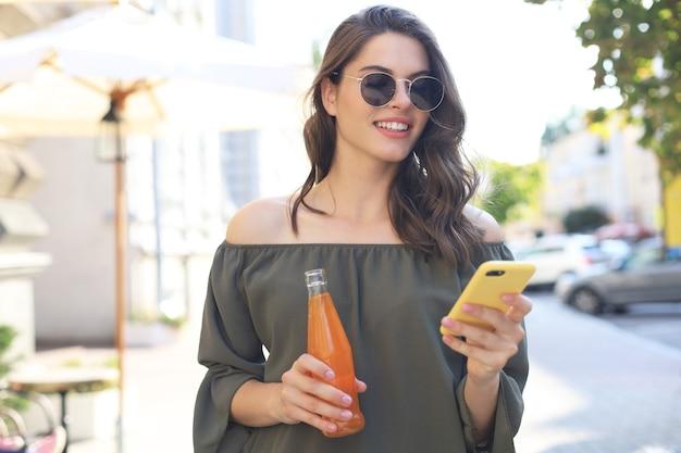 Привлекательная молодая женщина в солнцезащитных очках держит бутылку с соком, используя смартфон, на открытом воздухе.