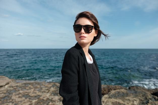 바람이 부는 날씨에 해변에 서있는 선글라스에 매력적인 젊은 여자