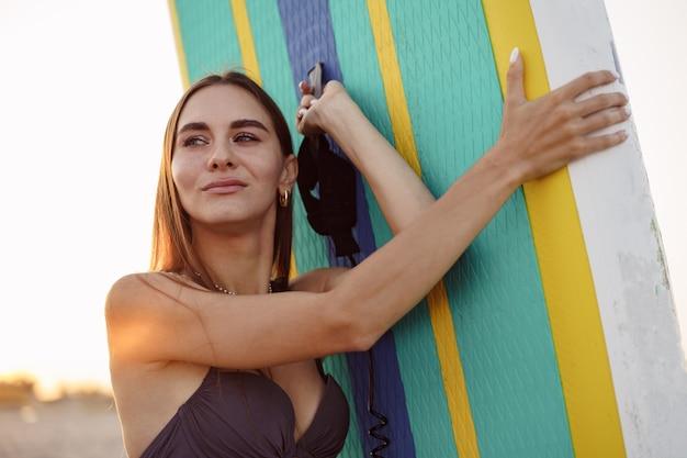 스탠드 업 패들 보드와 함께 포즈를 취하는 수영복에 매력적인 젊은 여자