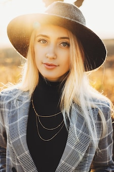 晴れた日に自然のぼやけた背景に立っている間カメラを見ている流行の帽子と市松模様のジャケットの魅力的な若い女性。自然の中で立っているスタイリッシュな女性