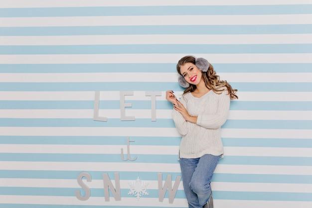 暖かいヘッドフォンで魅力的な若い女性はフレンドリーな笑顔。テキストに対する屋内の女の子の肖像画:「雪を降らせて」