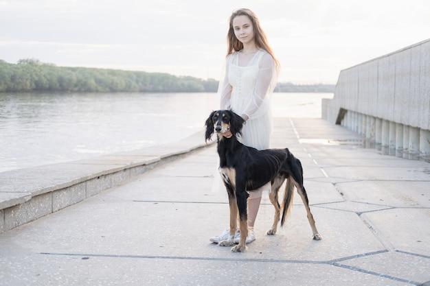 Привлекательная молодая женщина в белой прогулке стойки платья с собакой салюки в городе. у берега реки. персидская борзая. концепция ухода за домашними животными. любовь и дружба между человеком и животным.