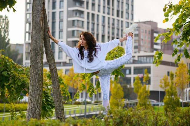白いレギンス、パーカー、スニーカーで魅力的な若い女性が木の幹に寄りかかって脚を伸ばし、屋外でトレーニング