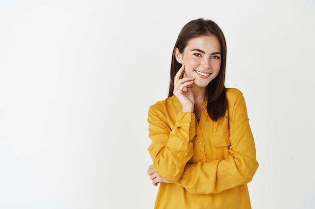 Привлекательная молодая женщина в желтой рубашке, улыбаясь и застенчиво глядя в камеру, стоя у белой стены