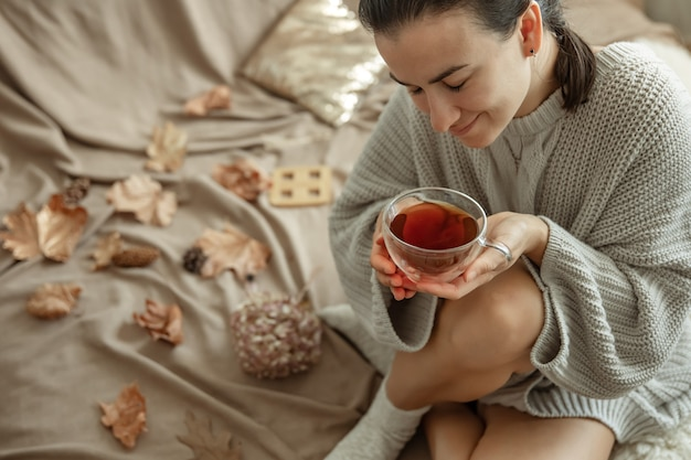 Attractive young woman is drinking tea sitting in bed among the autumn leaves