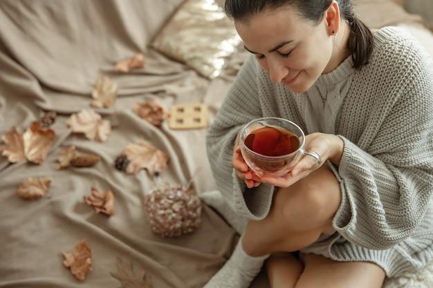 매력적인 젊은 여자가 단풍 사이 침대에 앉아 차를 마시고 있다