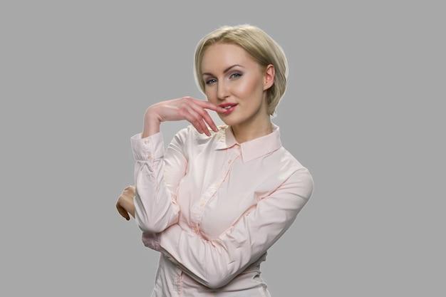 魅力的な若い女性がいちゃつくと誘惑しています。オフィスシャツのきれいな女性は、灰色の背景にポーズをとって彼女のセクシュアリティを表現しています。