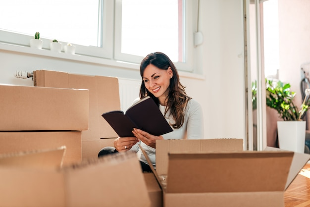 Attractive young woman is moving, reading book and smiling while packing.