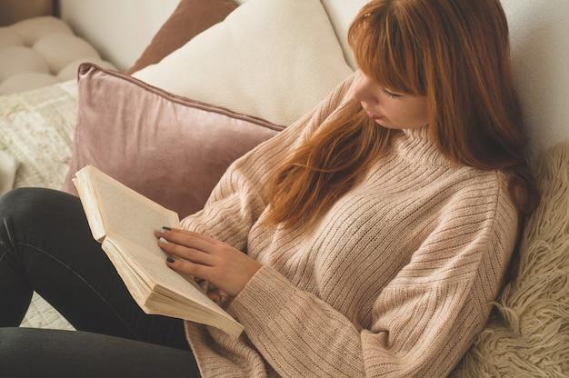 Привлекательная молодая женщина читает книгу дома