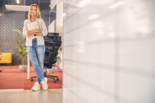 Attractive young woman in jeans smiling while holding spiral sketchbook. website banner
