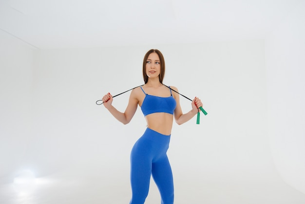 魅力的な若い女性は青いトラックスーツで縄跳び。フィットネス、健康的なライフスタイル。