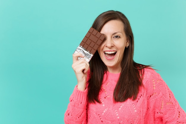Attractive young woman in knitted pink sweater hold in hand, covering eye with chocolate bar isolated on blue turquoise wall background, studio portrait. people lifestyle concept. mock up copy space.