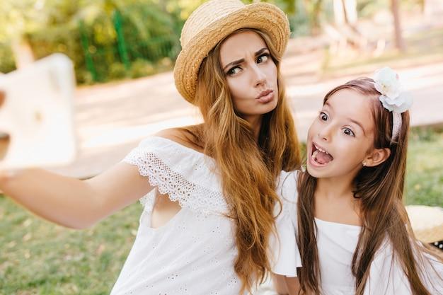 Attraente giovane donna in abito di pizzo scherzare con la figlia per la foto, mentre riposa nel parco. signora alla moda e bambina carina che fanno facce buffe per selfie.