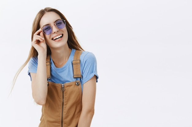 Attractive young woman laughing and feeling happy on vacation, wearing sunglasses