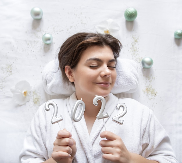 An attractive young woman lies in a white robe for a spa procedure, holds the numbers 2022 on a white background, the concept of christmas and new year.