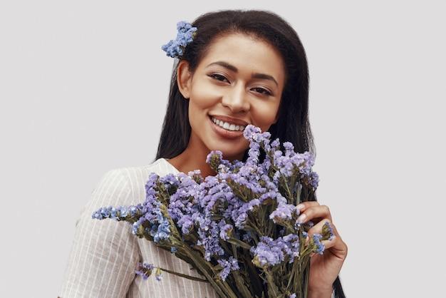 Привлекательная молодая женщина смотрит в камеру и улыбается, стоя на сером фоне