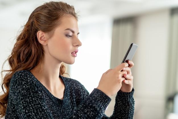 自宅でスマートフォンを見ている魅力的な若い女性。女性はスマートフォンでメッセージを入力します。