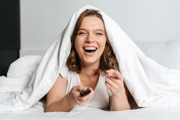 Attractive young woman lying in bed at home watching tv, laughing