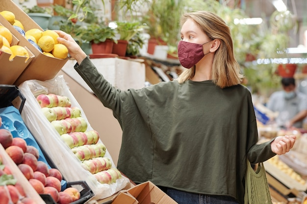 Attractive young woman in mask standing at counter and shopping for groceries during coronavirus