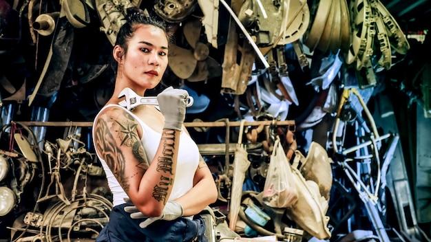 古いガレージでヴィンテージカーを修理する魅力的な若い女性の機械労働者。