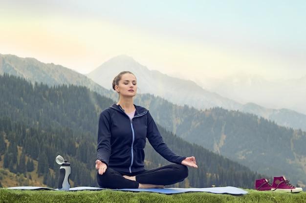 山で瞑想する魅力的な若い女性