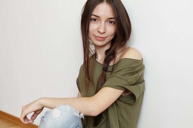 매력적인 젊은 여자 모델, 세련된 옷을 입고 바닥에 앉아 흰 벽에 기대어 그녀의 예쁜 얼굴에 친절하고 편안한 표정