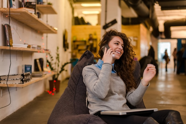 Attractive young woman in modern interior talking on phone.