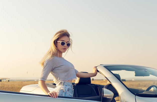 Attractive young woman near a convertible car