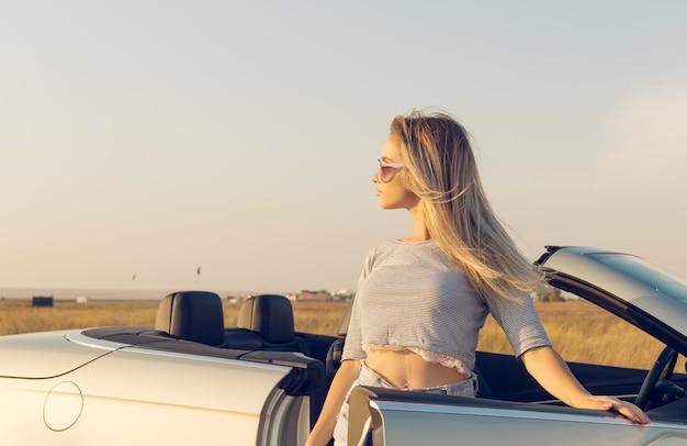 Attractive young woman near a convertible car
