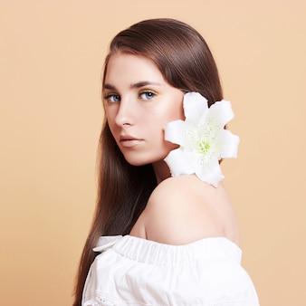 白い背景の上の魅力的な若い女性。白い花の花束を持つ美しい少女の肖像画。