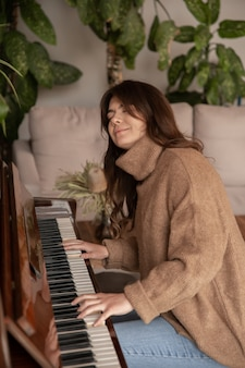An attractive young woman plays the piano