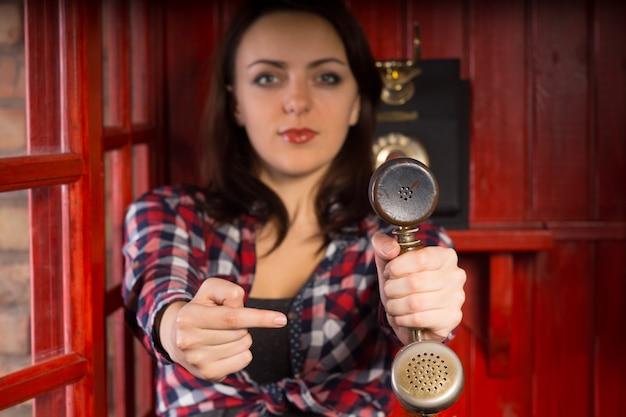 彼女が着信を示す有用なジェスチャーで視聴者に向かってそれを伸ばすときにヴィンテージの電話の携帯電話を指している魅力的な若い女性 Premium写真