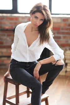 흰 셔츠와 청바지에 포즈 매력적인 젊은 여자