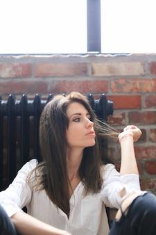 Привлекательная молодая женщина позирует в белой рубашке и джинсах Бесплатные Фотографии